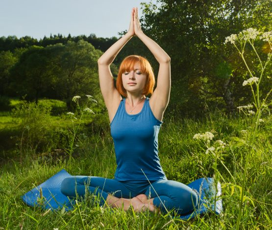 Beautiful red haired woman practicing fitness yoga outdoors on a summer day